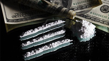 Lines of cocaine and rolled currency